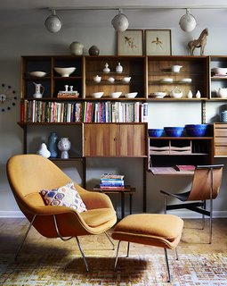 How to Update a Midcentury Modern Gem - Photo 7 of 12 - Illuminated by track lighting, a teak wall unit by Poul Cadovius showcases pottery by Eva Zeisel and Paul McCobb, among others. The desk seat is a T chair by William Katavolos, Ross Littell, and Douglas Kelley; the Womb chair is by Eero Saarinen for Knoll.