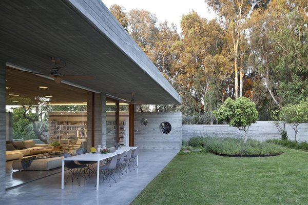 Modern home with outdoor, back yard, grass, concrete patio, porch, deck, and trees. Photo  of House of an Architect