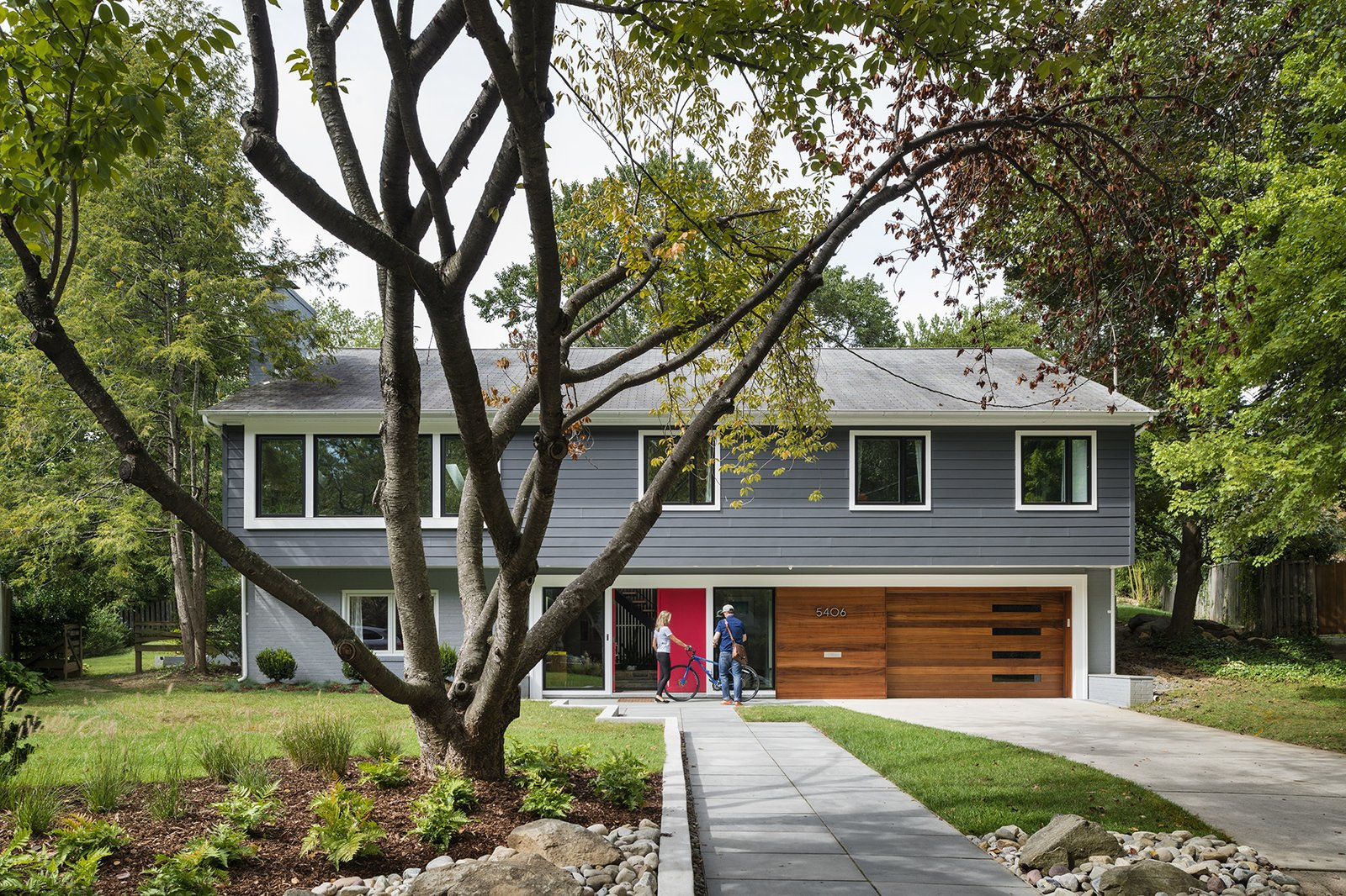 """""""We looked at so many colonials and couldn't imagine what we'd do with all the tiny rooms,"""" says Dianne Bruning, who with her husband, David Owen, enlisted architect Lou Balodemas to update a 1968 home outside of Chevy Chase, Maryland. Tagged: Front Yard, Trees, Shrubs, Grass, Hardscapes, Gardens, Walkways, Exterior, House, and Wood Siding Material.  Photo 2 of 8 in Minor Adjustments"""