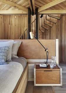 A Floating South African Cabin Borrows From the Landscape - Photo 7 of 9 - Like the built-in bed, nightstands, headboard, and other custom furniture, the staircase leading to the open-air viewing platform was made by Versfeld. The Lektor desk lamps are by Rubn.