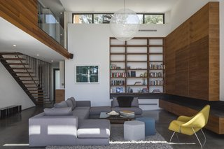 A Southern Californian Prefab Is Paradise For the Whole Family - Photo 2 of 11 - Jay and Jaclyn Lieber worked with Erla Dögg Ingjaldsdóttir and Tryggvi Thorsteinsson of Minarc to design a house using the designers' mnmMOD panels, which can be assembled with a screw gun. The core of the home was kept open to maximize natural light. Clerestory windows, walnut cabinetry, and concrete floors define the living room, which features a sectional by Jessica McClendon of Glamour Nest, who consulted on the furnishings, a Nesta rug from Design Within Reach, a Moooi Random Light from YLighting, and Hecks ottomans from Blu Dot.
