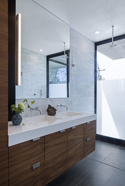 A Southern Californian Prefab Is Paradise For the Whole Family - Photo 5 of 11 - Silestone counters, walnut cabinetry, and Refin floor tiles accent the master bathroom. The Axor Uno faucets are from Hansgrohe, the Alinea vanity light is from Aamsco, and the shower head is by Jaclo.