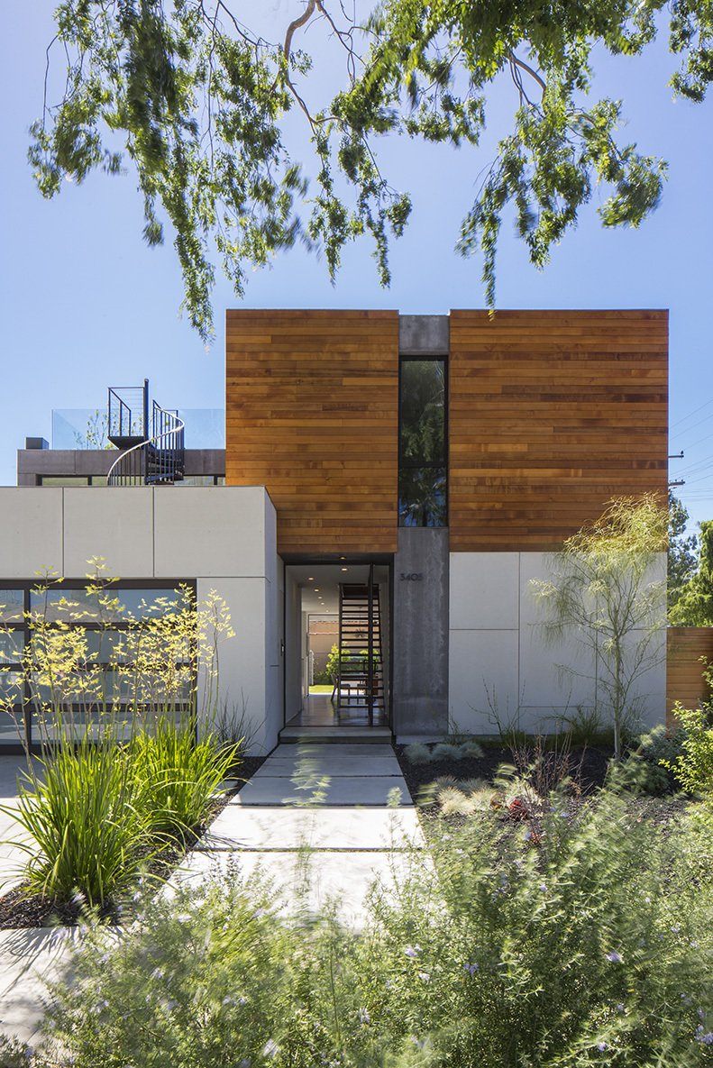 """The designers used wood sparingly for maximum effect, like the cedar siding on the front and back exteriors. The main facade offers  a glimpse through the house to the backyard, which was made larger by placing the garage closer to the street. """"We hosted a concert and had people sitting inside and in front of the pool,"""" says Jaclyn. """"The house completely lends itself to entertaining small and large groups alike."""" Tagged: Outdoor, Shrubs, Grass, Hardscapes, Front Yard, Gardens, and Walkways. A Southern Californian Prefab Is Paradise For the Whole Family - Photo 11 of 12"""