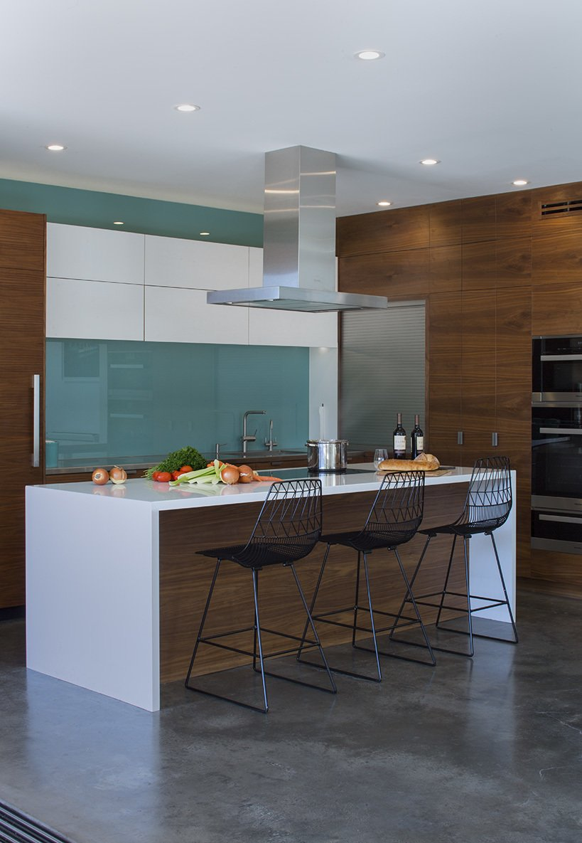 In the kitchen, a blue glass backsplash evokes the designers' native Iceland. The  Bend Goods stools are from YLiving.