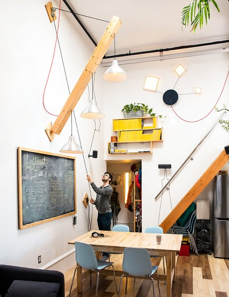 """Modern home with dining room, table, chair, ceiling lighting, pendant lighting, and medium hardwood floor. Max devised a movable plywood beam that holds a trio of pendant lamps to swing down as needed.  A wood piece covered in chalkboard paint hides the electrical panel. """"Slate was too expensive,"""" he says. Photo 3 of Max's Apartment"""