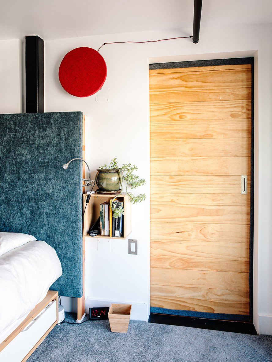 For his bedroom, Max designed a custom headboard insulated with several layers of cotton and upholstery fabric to reduce sound. Tagged: Bedroom, Carpet Floor, and Bed.  Max's Apartment by Dwell from Devising Clever Solutions For a Small San Francisco Loft