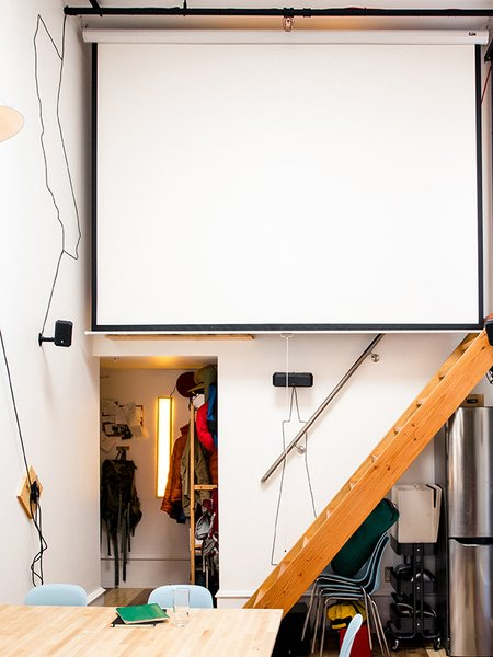 """Modern home with staircase and wood tread. Max likes to do screenings for friends: """"The first time I hosted I showed Planet Earth. Next up is Koyaanisqatsi: Life Out of Balance, a 1982 experimental film by Godfrey Reggio with music by Philip Glass."""" Photo 9 of Max's Apartment"""