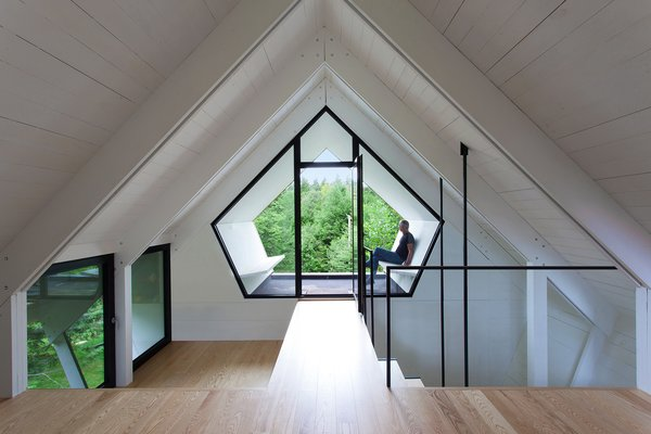 Modern home with hallway and light hardwood floor. The pentagonal geometry of the  third story is echoed by an Alumilex  window. Photo 4 of La Colombière