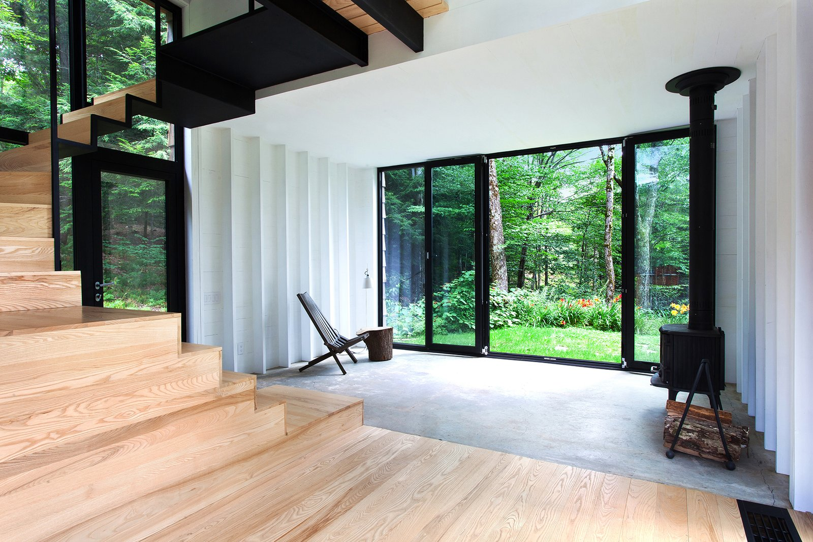 The addition rises  above the original shack's 400- square-foot concrete foundation, which is partially visible in the  living room. A Cricket patio chair by Hershy Way is used for indoor seating opposite a Morsø wood-burning stove.