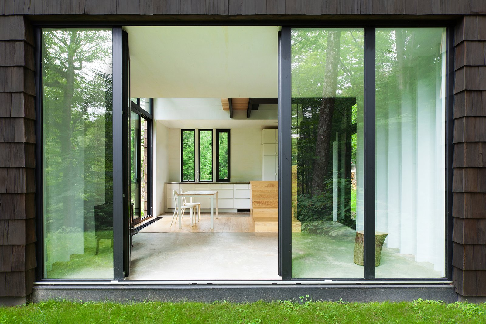 The interior is spare and modern. The cabinets and chairs are from IKEA. So is the table, which has a DIY laminated-ash top. Suzanne Rochon bought the cabin in 2002 and spent a decade fixing it up before calling on YH2 Architecture. In 2005, she added five acres, doubling the property.