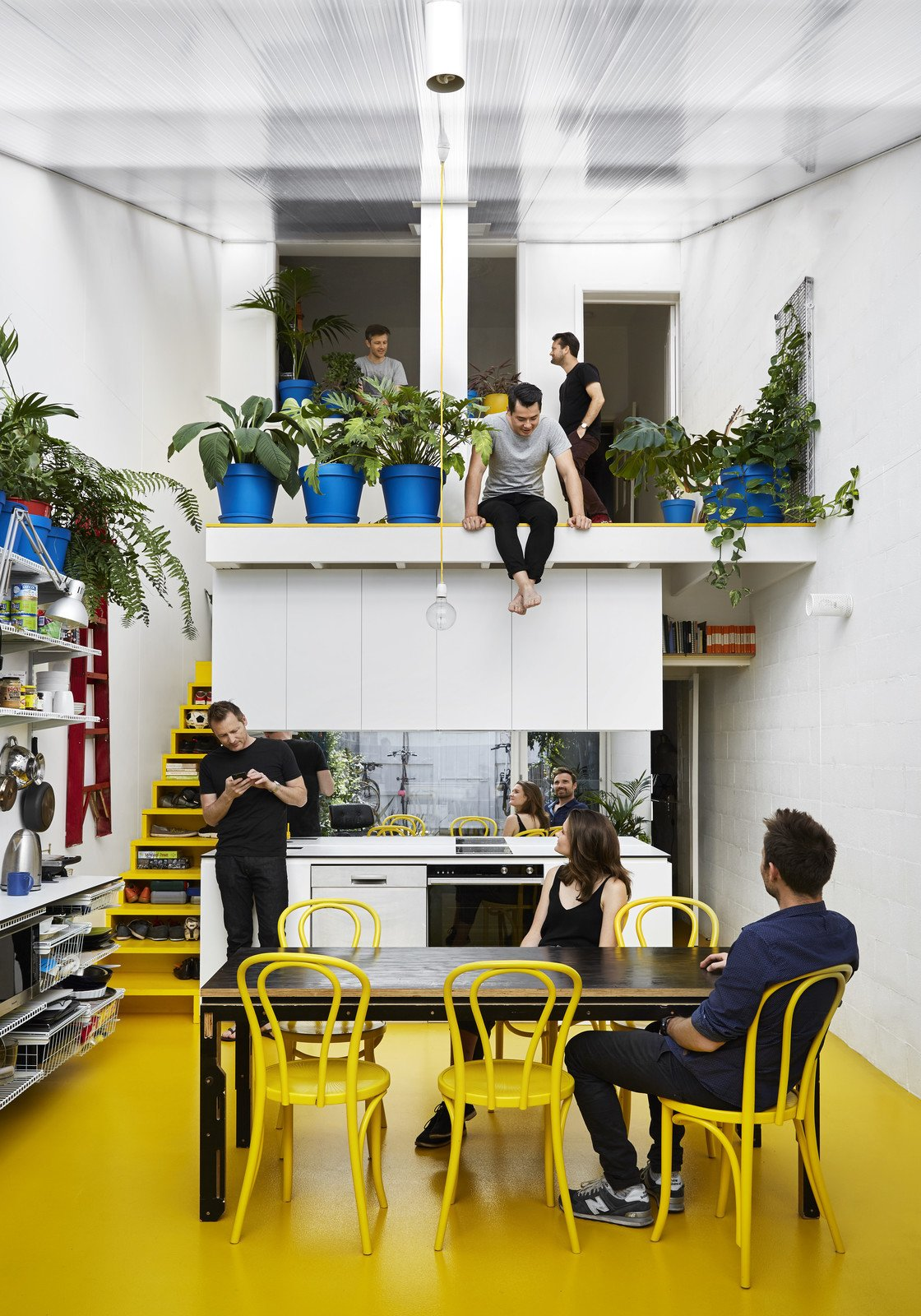 In an attempt to beat the winter blues and improve his work/life balance, Australian architect Andrew Maynard combines his home with his office in a sun-drenched Victorian terrace with bright bursts of yellow. In 2016, architect Andrew Maynard of Austin Maynard Architects (AMA) decided to transform the way he and his team live and work. At the end of winter, Maynard visited a doctor about his increasing levels of stress and anxiety. The doctor's suggestion was that he get more vitamin D to improve his mental health. Maynard decided to radically renovate his dark, Victorian-style terrace house in Melbourne, and flood it with therapeutic sunshine. Tagged: Dining Room, Chair, Linoleum Floor, and Table.  Photo 2 of 12 in An Architect Turns His Victorian Home Into a Sun-Drenched Live/Work Space