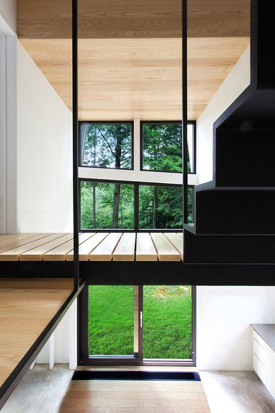 Modern home with hallway and light hardwood floor. The second floor is a master bedroom, bathroom, and mechanical room, along with an open volume that fills the house with light from the Alumilex doors and windows. The paint is Distant Gray by Benjamin Moore. Photo 7 of La Colombière