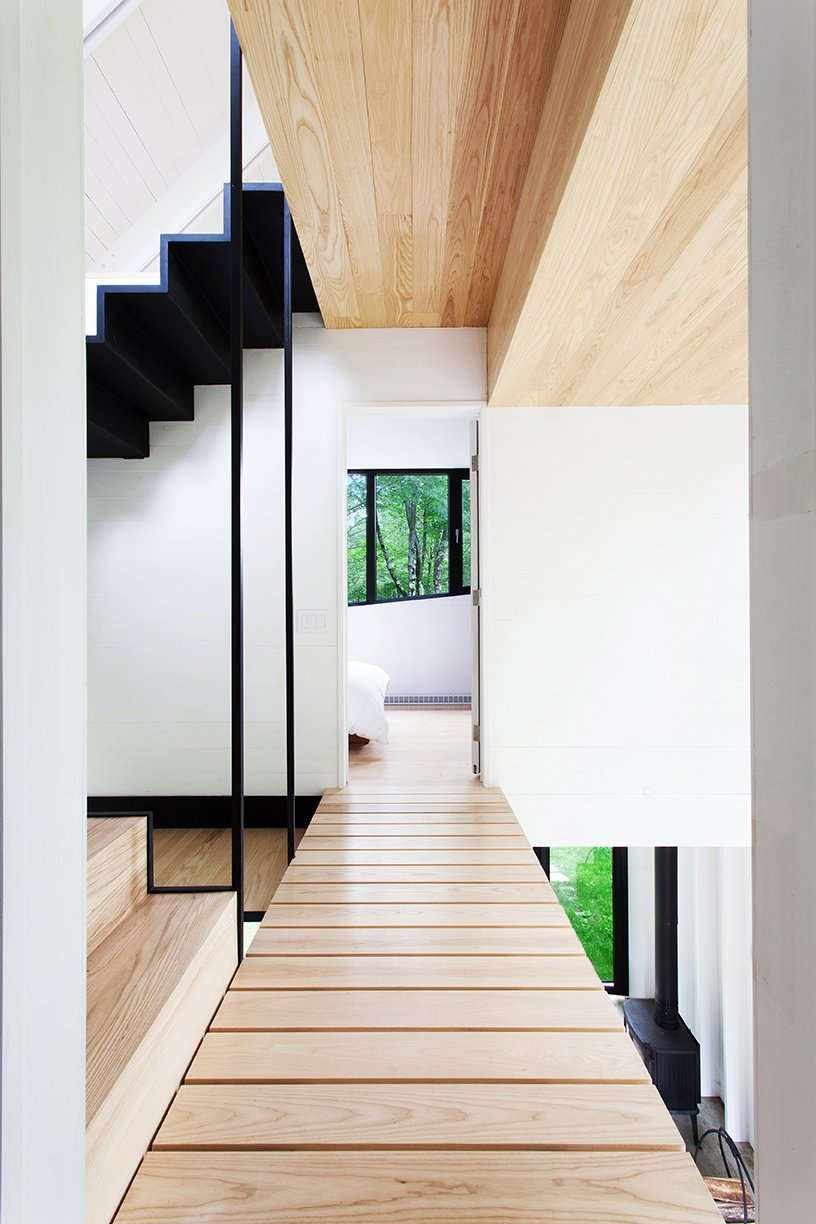 Architects Marie-Claude Hamelin and Loukas Yiacouvakis connected the home's three levels in dramatic fashion. Ash treads float on a steel stringer from the ground floor to the mezzanine. Tagged: Hallway and Light Hardwood Floor.  Photo 6 of 11 in Growing Upward and Outward, a Cabin Expansion Mirrors the Trees