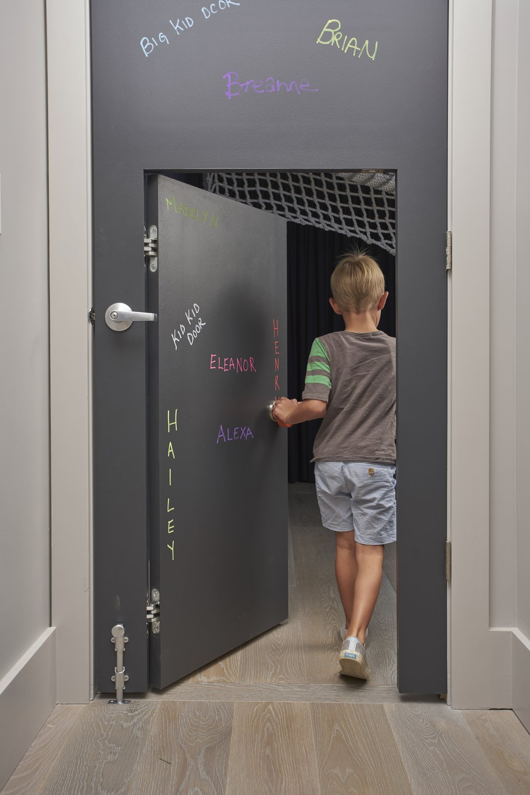 In certain places, the scale of the home is adjusted for children. A standard door, covered in chalk-board paint, has a 48-inch-tall door set inside it. Tagged: Kids Room, Toddler Age, Neutral Gender, and Playroom.  Photo 6 of 9 in Child's Play: Designing a Polished, All-Ages Playscape