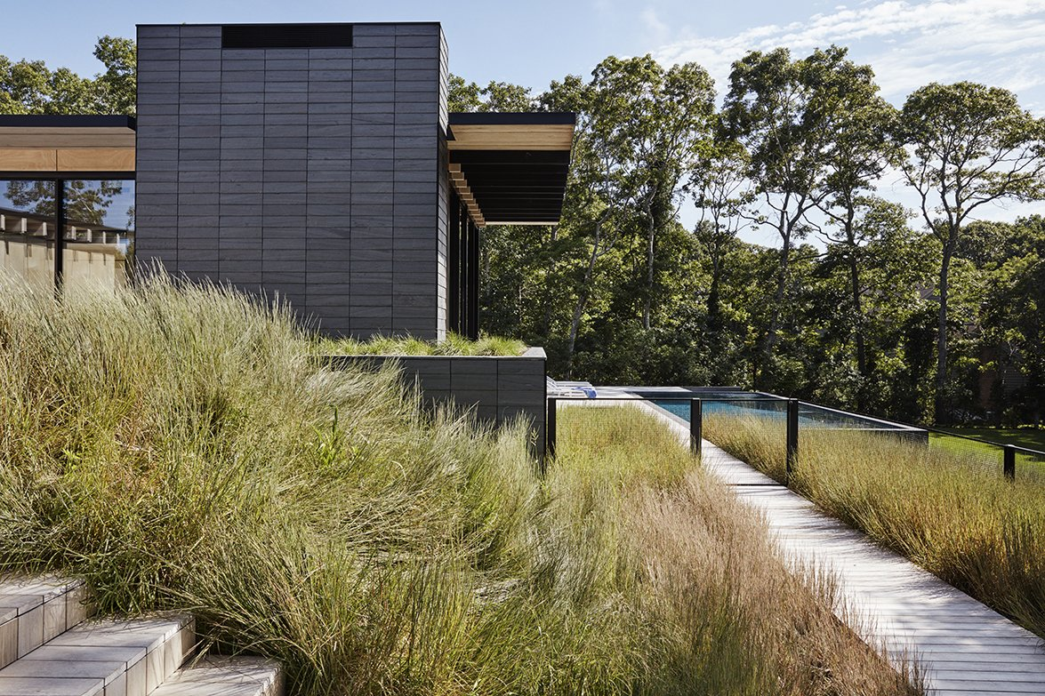A tight pattern of slate cladding complements a wild carpet of native grasses outside an East Hampton residence by Paul Masi of Bates Masi + Architects. The home, sited to capture the breeze, was constructed for a family of wind-sports enthusiasts.