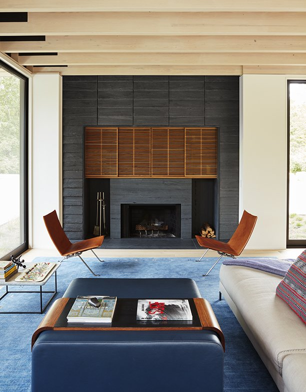 Masi used the same gray slate for the exterior and the fire surround, which boasts a custom wood inset by K. Romeo Inc. The living room also features a custom area rug by SandH Rugs, a Charles sofa by B&B Italia, a pair of PK22 leather chairs by Poul Kjærholm from Fritz Hansen, and an Obi coffee table and tray by Lumifer.