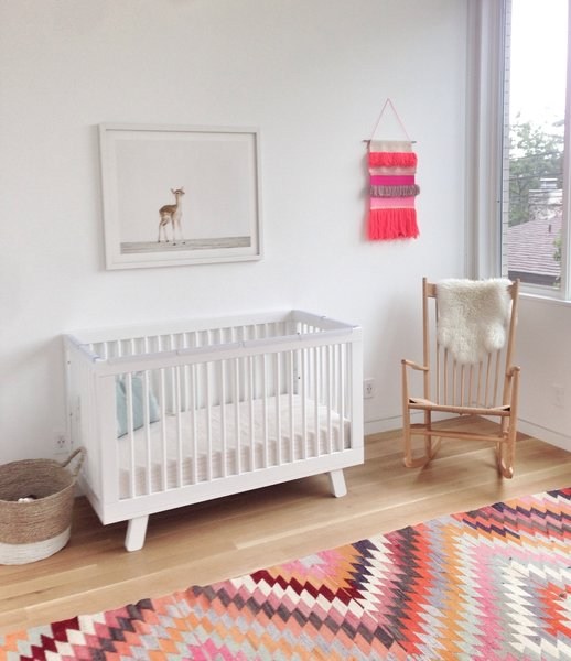 The resident's daughter, Clara, has a Hudson crib by Babyletto, a vintage J16 rocker by Hans Wegner, and a vintage rug in her bedroom.