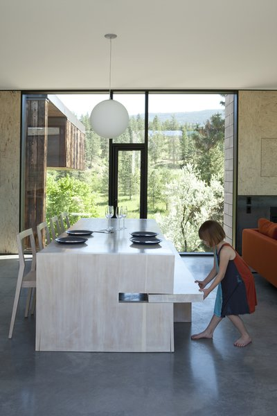A custom table designed by Jones features a pull-out bench on one side and 1C dining chairs by Room B on the other; the Globo pendant is by Viso. Tagged: Dining Room, Chair, Concrete Floor, Pendant Lighting, and Table.  Photo 6 of 11 in A Hilltop Home in British Columbia That Seems to Grow Out of a Park