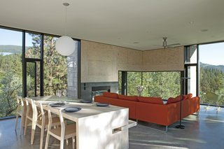 A Hilltop Home in British Columbia That Seems to Grow Out of a Park - Photo 6 of 10 - The living area includes a red Canyon sectional by Bensen and a Pensi ceiling fan by Modern Fan Company.