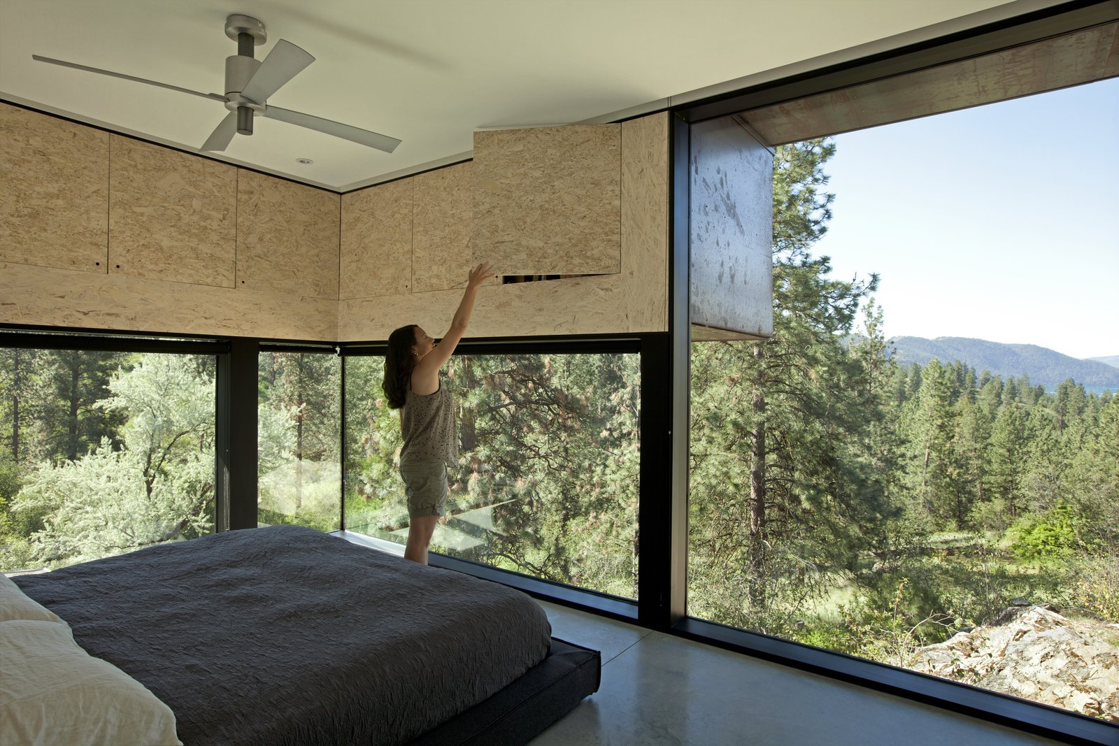 Protruding overhead cupboards increase storage space and reduce solar gain. The bed is Dodu by Blu Dot. Tagged: Bedroom, Bed, and Concrete Floor.  Photo 8 of 11 in A Hilltop Home in British Columbia That Seems to Grow Out of a Park