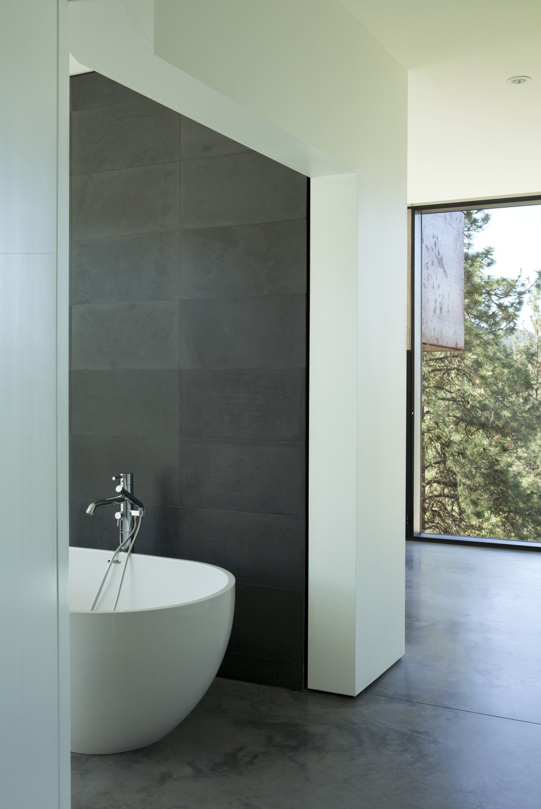 The bathtub is Aquabagno by Aquabrass. Tagged: Bath Room, Concrete Floor, Freestanding Tub, and Concrete Counter. A Hilltop Home in British Columbia That Seems to Grow Out of a Park - Photo 10 of 11