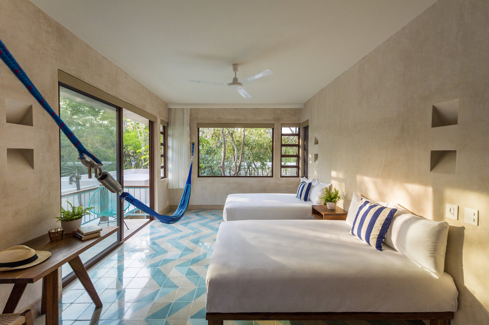 Designed in an architectural style that was popular in the Miami Beach area in the 1950s, the hotel—with its rattan chairs and soothing aquamarine palette—is a pared-down, retro-inspired jungle oasis.  All the floor tiles were designed by Haag who had them custom-made in Guadalajara with Mooma Mosaicos. The walls in the guest rooms were made with local sand mixed with white cement. A type of local limestone, known as Mayan stone, was used for the feature wall at the back of the bar. A water bio-digester treatment plant was incorporated so that water can be treated on-site and used for watering the lush gardens surrounding the property. Tagged: Bedroom, Night Stands, Ceiling Lighting, Bed, and Ceramic Tile Floor.  Photo 5 of 9 in A New Modern Hotel Brings Midcentury Miami to Tulum, Mexico