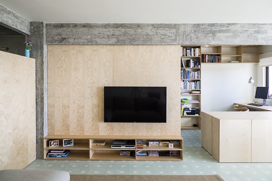 The living room is defined by a large birch plywood television console, designed by architect, Miguel Marcelino. - Lisbon, Portugal Dwell Magazine : July / August 2017 Tagged: Living Room, Bookcase, Media Cabinet, Storage, Desk, and Ceramic Tile Floor.  The Henriques/Moreira Residence by Dwell from Lisbon Vision