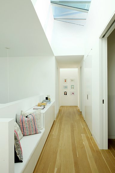 Modern home with hallway and medium hardwood floor. Large skylights provide an abundance of natural light. The operable skylights are by Industrial Skylights. Photo 8 of The Ro Residence