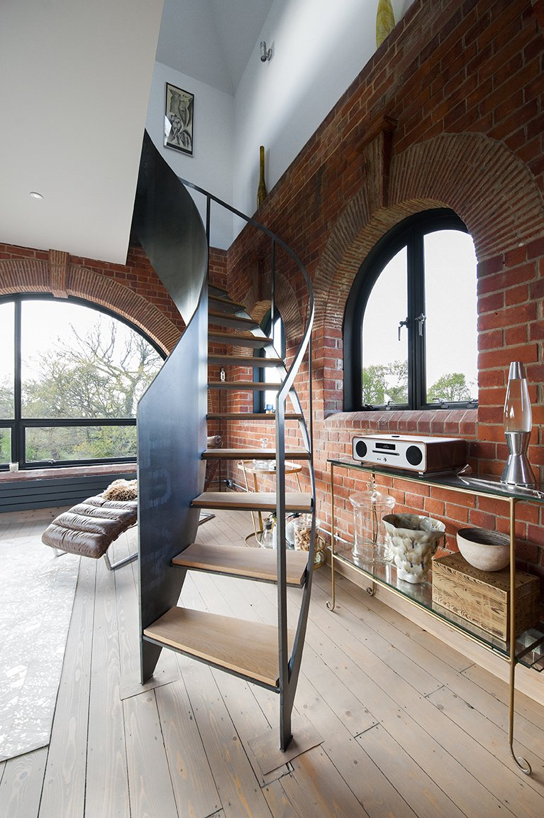Littlehampton Welding made the steel staircase on the third floor. Tagged: Chair, Light Hardwood Floor, Console Tables, Staircase, Metal Railing, and Wood Tread.  Lister Tower by Dwell from A Refurbished Victorian-Era Brick Tower in Hampshire