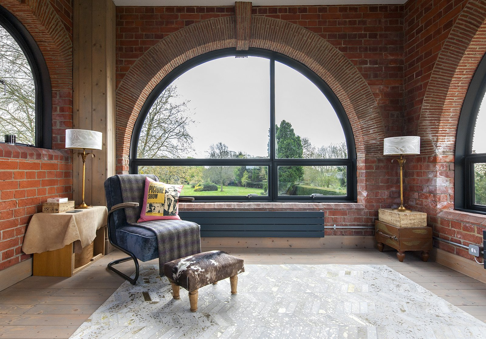 The facade is punctuated by windows of various shapes, including half-moons by Crittall. The armchair and chevron rug are from Graham & Green. Tagged: Living Room, Table Lighting, End Tables, Chair, Lamps, and Light Hardwood Floor.  Lister Tower by Dwell from A Refurbished, Victorian-Era Brick Tower in Hampshire