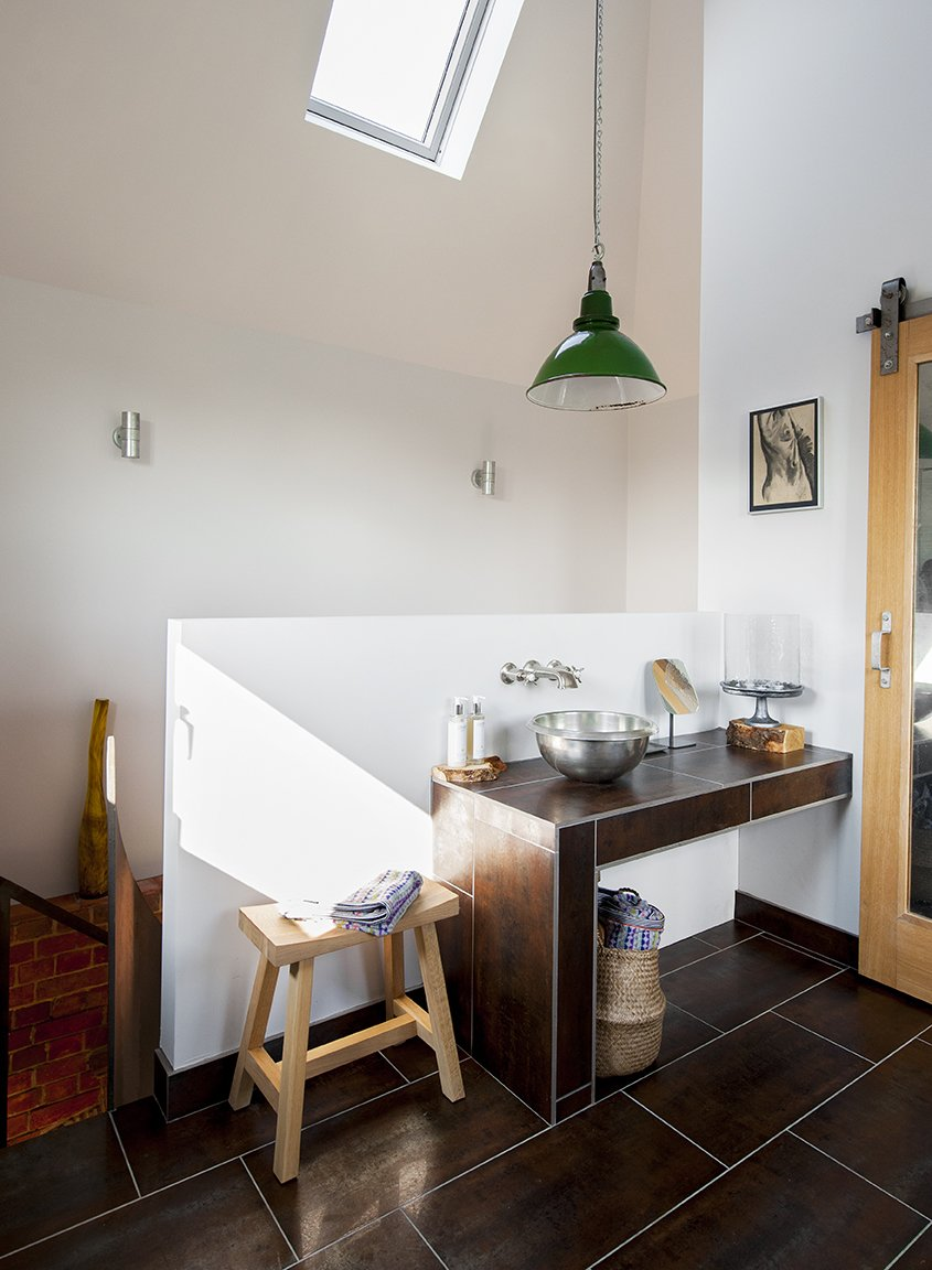 The bathroom occupies the highest chamber of the tower. A vintage pendant purchased from Skinflint Design hangs above a copper sink  by William Holland. Tagged: Bath Room, Vessel Sink, and Pendant Lighting.  Lister Tower by Dwell from A Refurbished, Victorian-Era Brick Tower in Hampshire