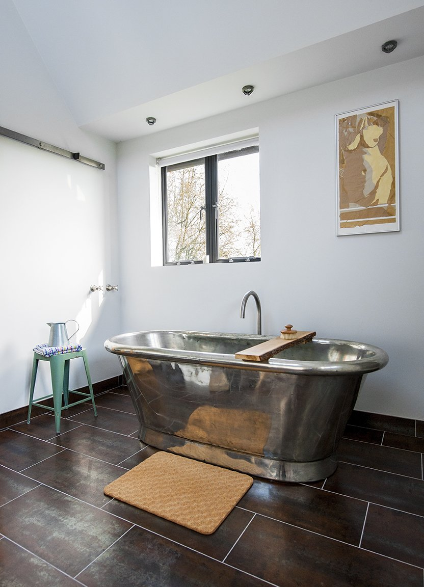 A freestanding copper tub, also by William Holland, sits exposed in a corner of the bathroom. The matching tile for the vanity and floor is by Marco Polo. Tagged: Bath Room, Freestanding Tub, and Ceiling Lighting.  Lister Tower by Dwell from A Refurbished Victorian-Era Brick Tower in Hampshire