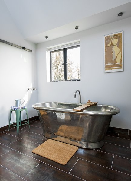 A freestanding copper tub, also by William Holland, sits exposed in a corner of the bathroom. The matching tile for the vanity and floor is by Marco Polo.