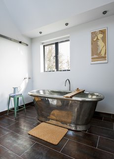 A Refurbished, Victorian-Era Brick Tower in Hampshire - Photo 7 of 9 - A freestanding copper tub, also by William Holland, sits exposed in a corner of the bathroom. The matching tile for the vanity and floor is by Marco Polo.