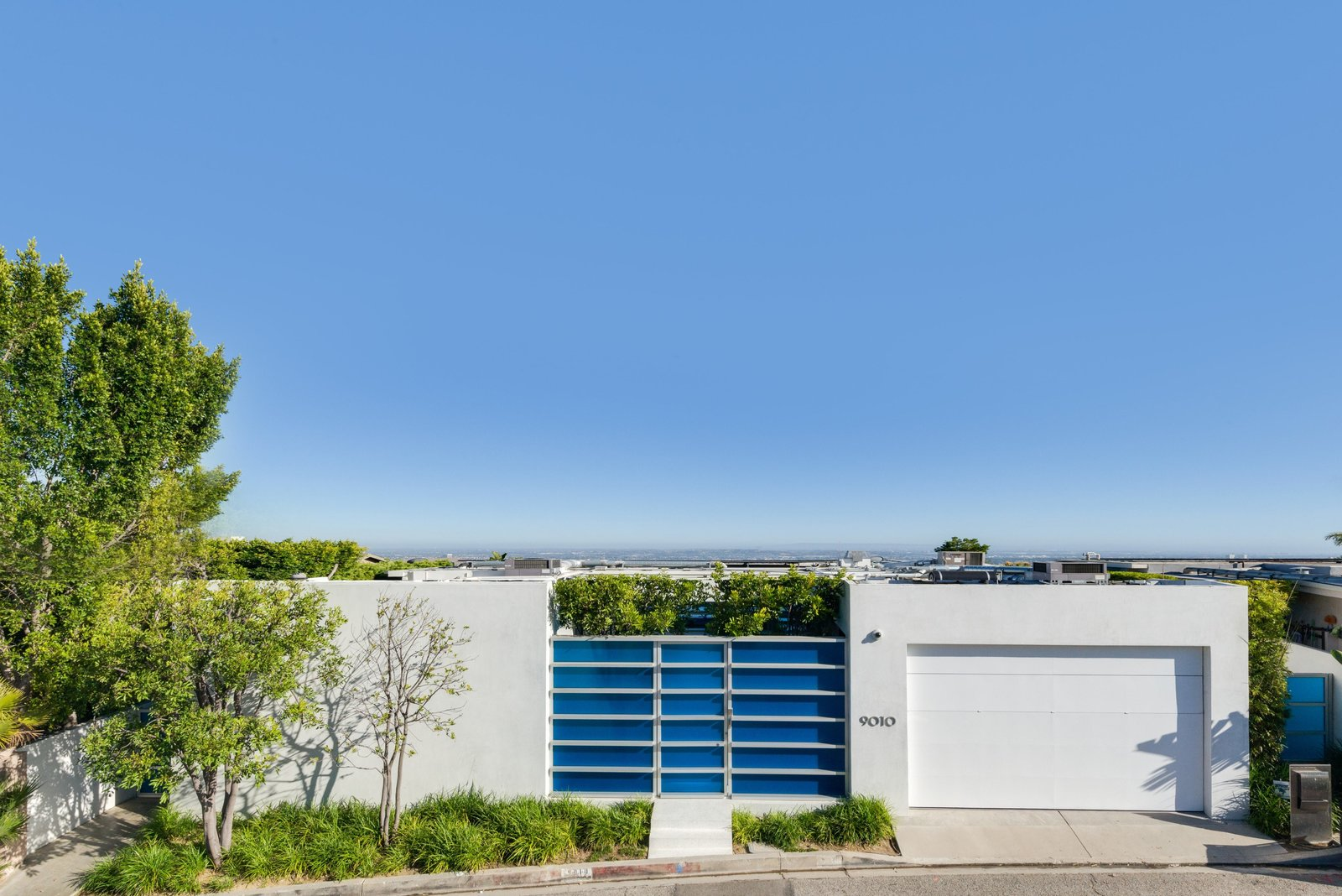 Tagged: Outdoor, Trees, Shrubs, Front Yard, and Metal Fences, Wall.  Hopen Place by Dwell from 'Friends' Star Matthew Perry's Midcentury Stunner in the Hollywood Hills Is For Sale