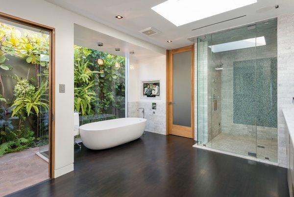 Modern home with bath room, freestanding tub, ceiling lighting, dark hardwood floor, full shower, and stone tile wall. Photo 8 of Hopen Place