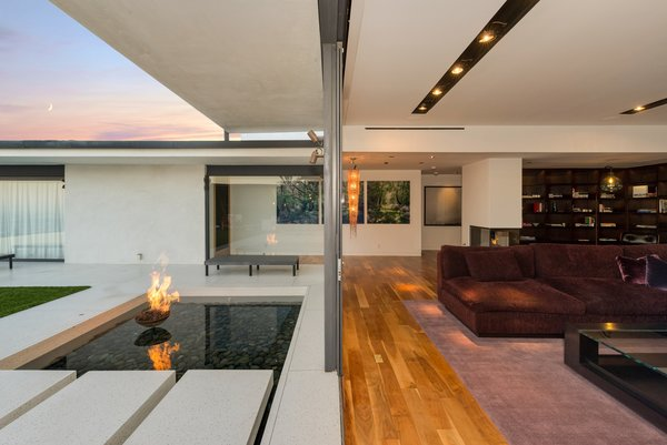 Modern home with living room, coffee tables, sectional, medium hardwood floor, ceiling lighting, and two-sided fireplace. Photo 10 of Hopen Place