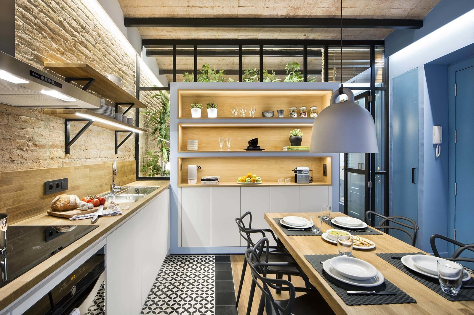 Tagged: Kitchen, Wood Counter, Wood Backsplashe, Pendant Lighting, Dishwasher, Range, Ceiling Lighting, Drop In Sink, Range Hood, and Ceramic Tile Floor.  Photo 1 of 11 in A Smart Layout Maximizes Space in This Compact Urban Beach Apartment in Barcelona