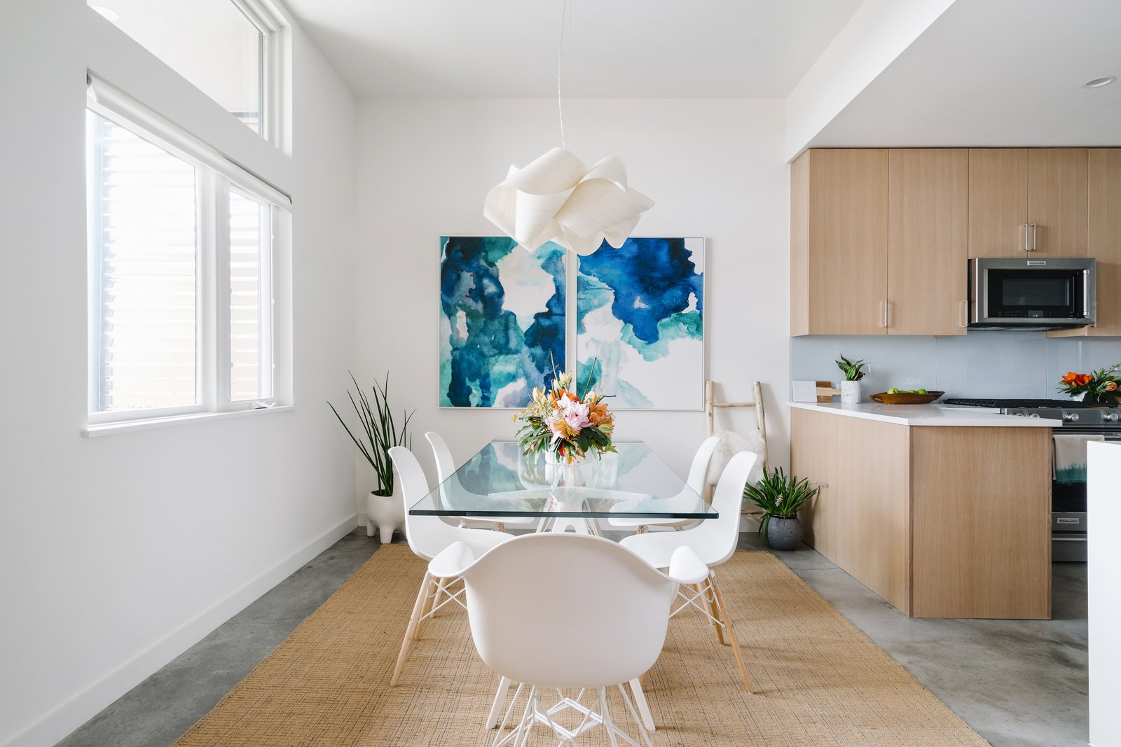 The dining room is outfitted with a pair of striking paintings by Vivian Caits.
