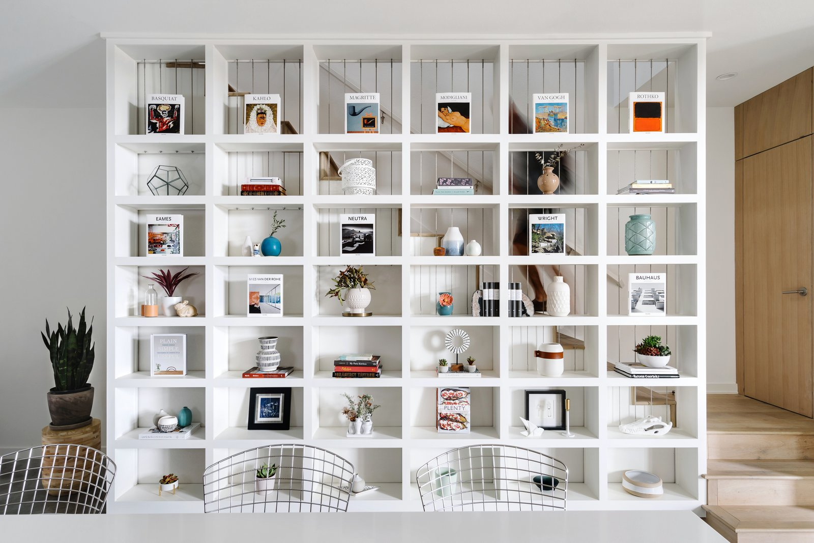 The large built-in shelving unit acts as a divider between the dining space and the staircase. Tagged: Storage Room and Shelves Storage Type.  Photo 3 of 7 in St. Barts-Inspired Accents Create Modern Tranquility in an Austin Tilley Row Home
