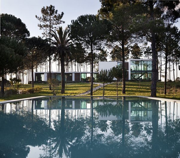 Modern home with outdoor, front yard, large pool, trees, and grass. Photo  of Villa Caetana