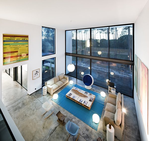 Modern home with living room, coffee tables, lamps, sofa, chair, pendant lighting, stools, floor lighting, and concrete floor. Photo 4 of Villa Caetana