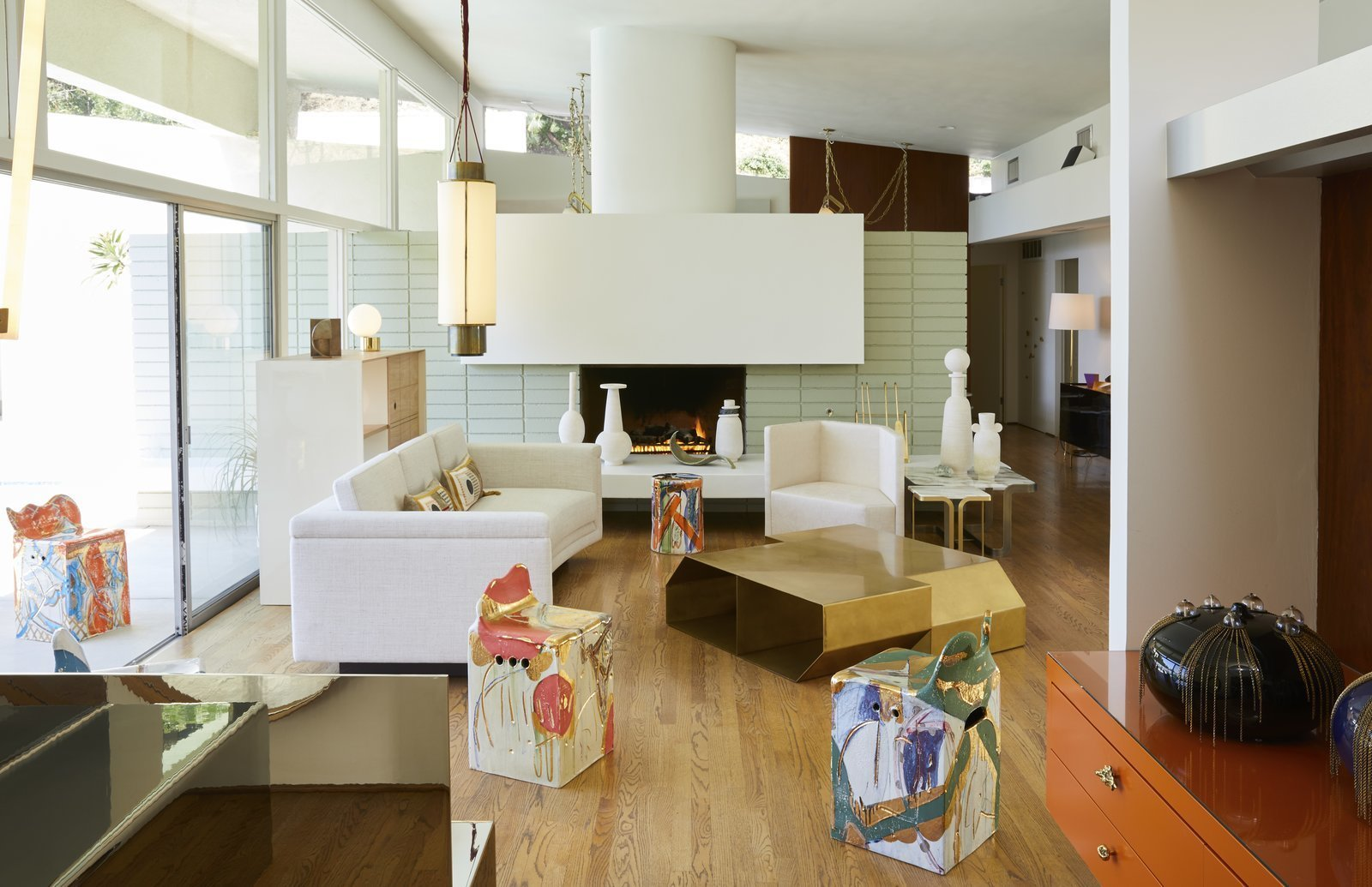 The bright and airy gallery space with a contemporary fireplace, sliding glass doors and a backyard pool serves as the perfect setting for Sanguino's work. Tagged: Living Room, Chair, Sofa, Table, Wood Burning Fireplace, Pendant Lighting, Standard Layout Fireplace, and Medium Hardwood Floor. Casa Perfect Debuts Reinaldo Sanguino's Vibrant Ceramics Inspired by '90s Graffiti Culture - Photo 2 of 10