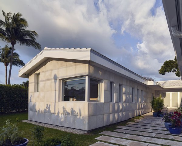 A 450-square-foot addition reconfigured the ranch house from an  L- to a U-shape. - Miami, Florida Dwell Magazine : July / August 2017 Tagged: Outdoor, Shrubs, Grass, Front Yard, Raised Planters, Walkways, and Hardscapes.  Photo 4 of 12 in A Professor and Designer Tests a New Hybrid Material on His Miami Beach Home