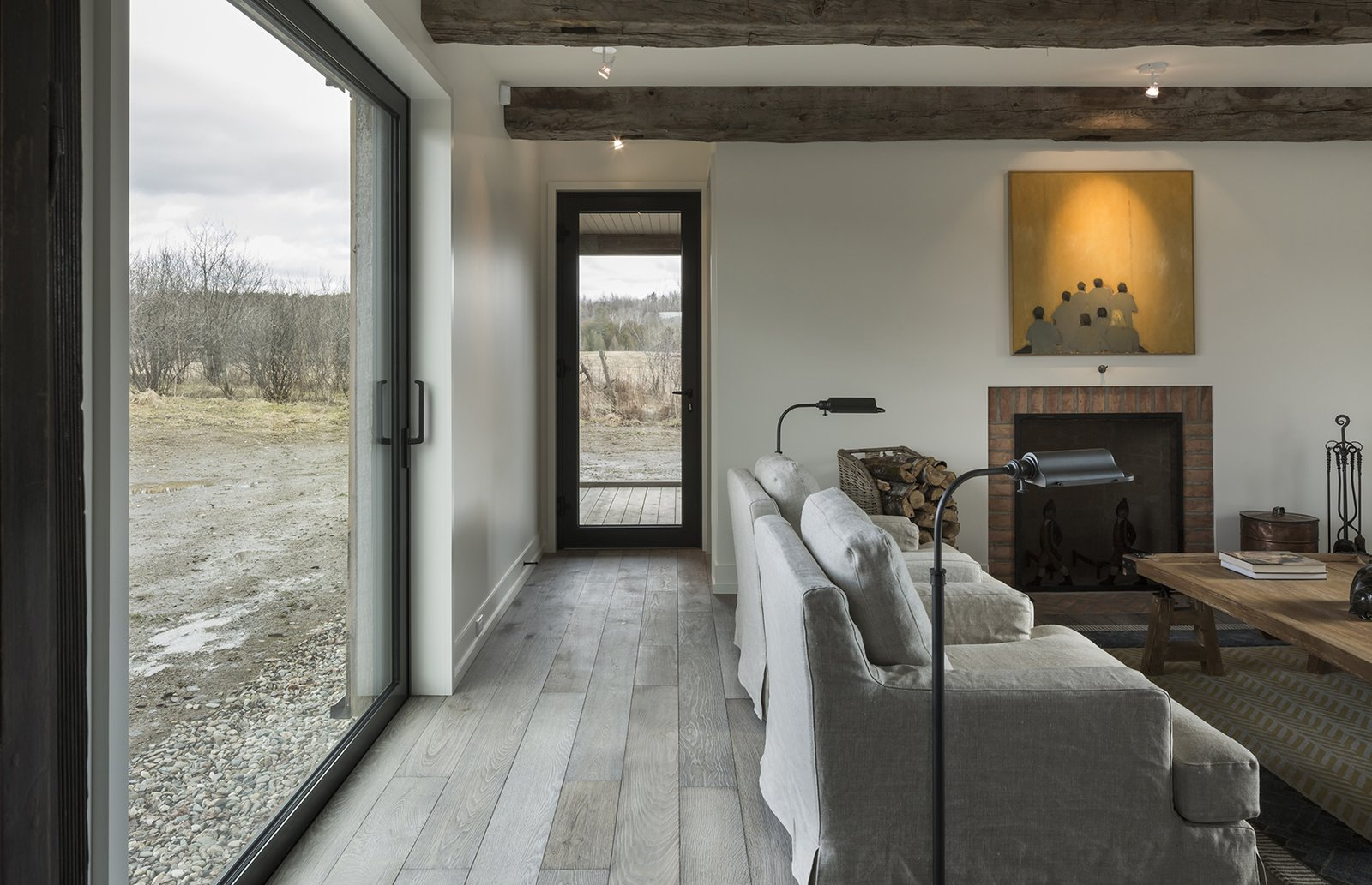 """""""We were researching places where we could get fake old beams, but at the last minute, the contractor found some from a barn that was coming down, Tagged: Living Room, Chair, and Table.  Photo 4 of 12 in An Artist and Farmer Work With a Toronto-Based Studio to Build a Barn-Inspired Home"""