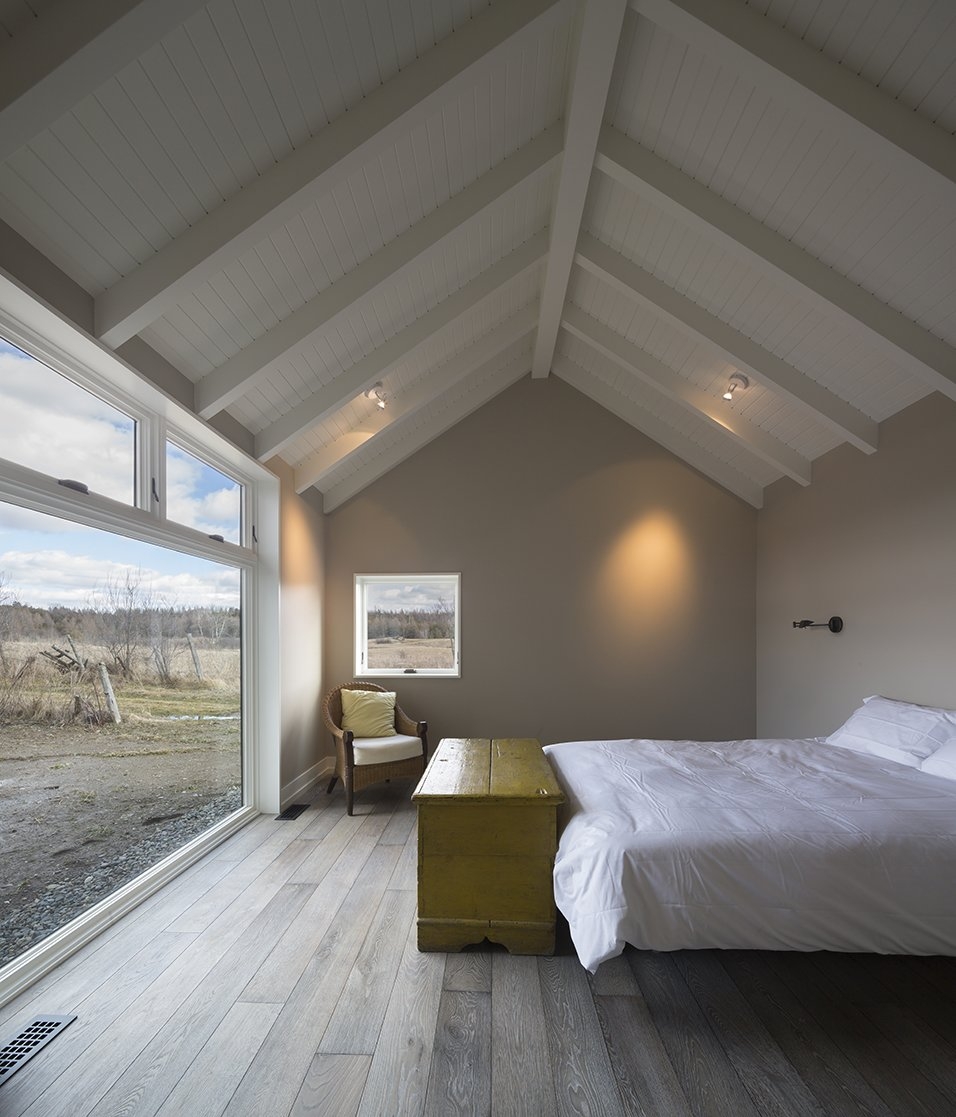 """The LAMAS team studied local and regional vernacular before beginning the design. """"Many of the towns around here have a New England architecture. It's more Vermont-looking than the typical Quebec village, - North Hatley, Quebec Dwell Magazine : July / August 2017 Tagged: Bedroom, Chair, Storage, Bed, Ceiling Lighting, and Light Hardwood Floor.  Photo 6 of 12 in An Artist and Farmer Work With a Toronto-Based Studio to Build a Barn-Inspired Home"""