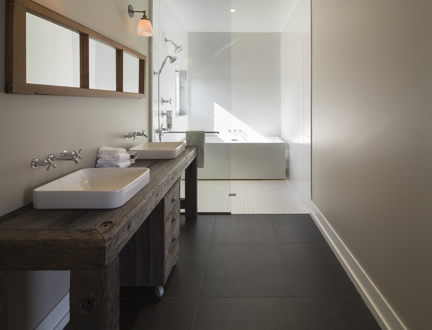 The master bathroom features sinks and fixtures by Kohler. The tub is by Aktuell. Tagged: Bath Room, Wood Counter, Open Shower, Freestanding Tub, and Vessel Sink.  Photo 9 of 12 in An Artist and Farmer Work With a Toronto-Based Studio to Build a Barn-Inspired Home