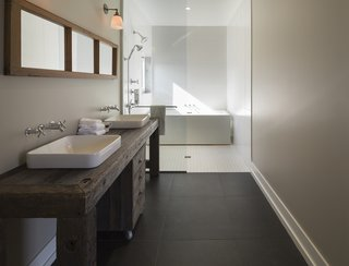 An Artist and Farmer Work With a Toronto-Based Studio to Build a Barn-Inspired Home - Photo 8 of 11 - The master bathroom features sinks and fixtures by Kohler. The tub is by Aktuell.