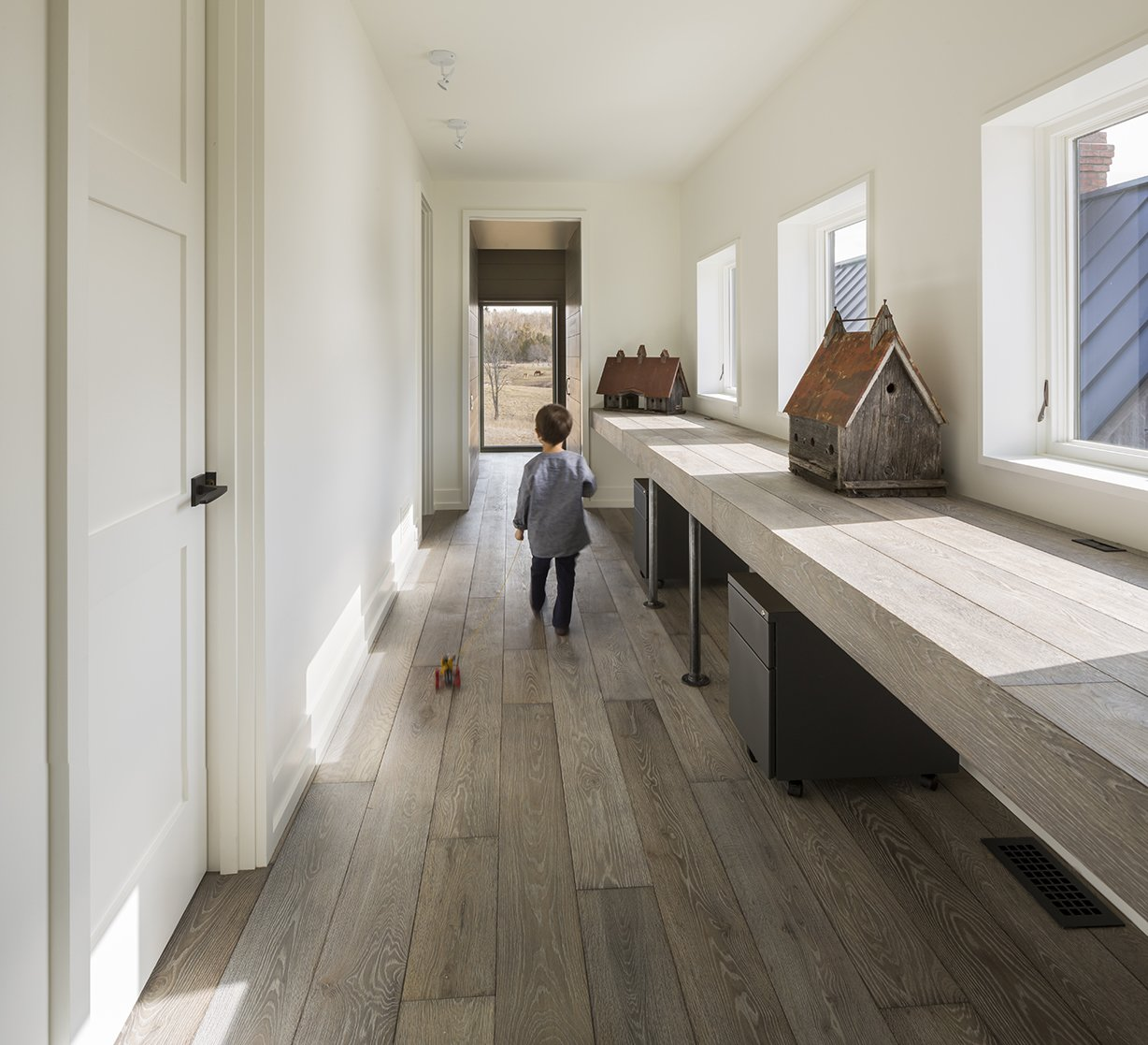 Antique-looking birdhouses are displayed in a hallway office space upstairs. - North Hatley, Quebec Dwell Magazine : July / August 2017 Tagged: Hallway and Medium Hardwood Floor.  Photo 10 of 12 in An Artist and Farmer Work With a Toronto-Based Studio to Build a Barn-Inspired Home