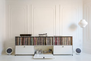 A Pair of Designers Renovate Their Brooklyn Brownstone With a Bright Monochromatic Palette - Photo 6 of 12 - The large front parlor was turned into a music room that flows seamlessly into a long dining room. A USM credenza holds vinyl and booze. Music flows via a Pro-Ject Debut III turntable, a pair of Elipson Planet L speakers, and a Music Hall Audio amplifier.